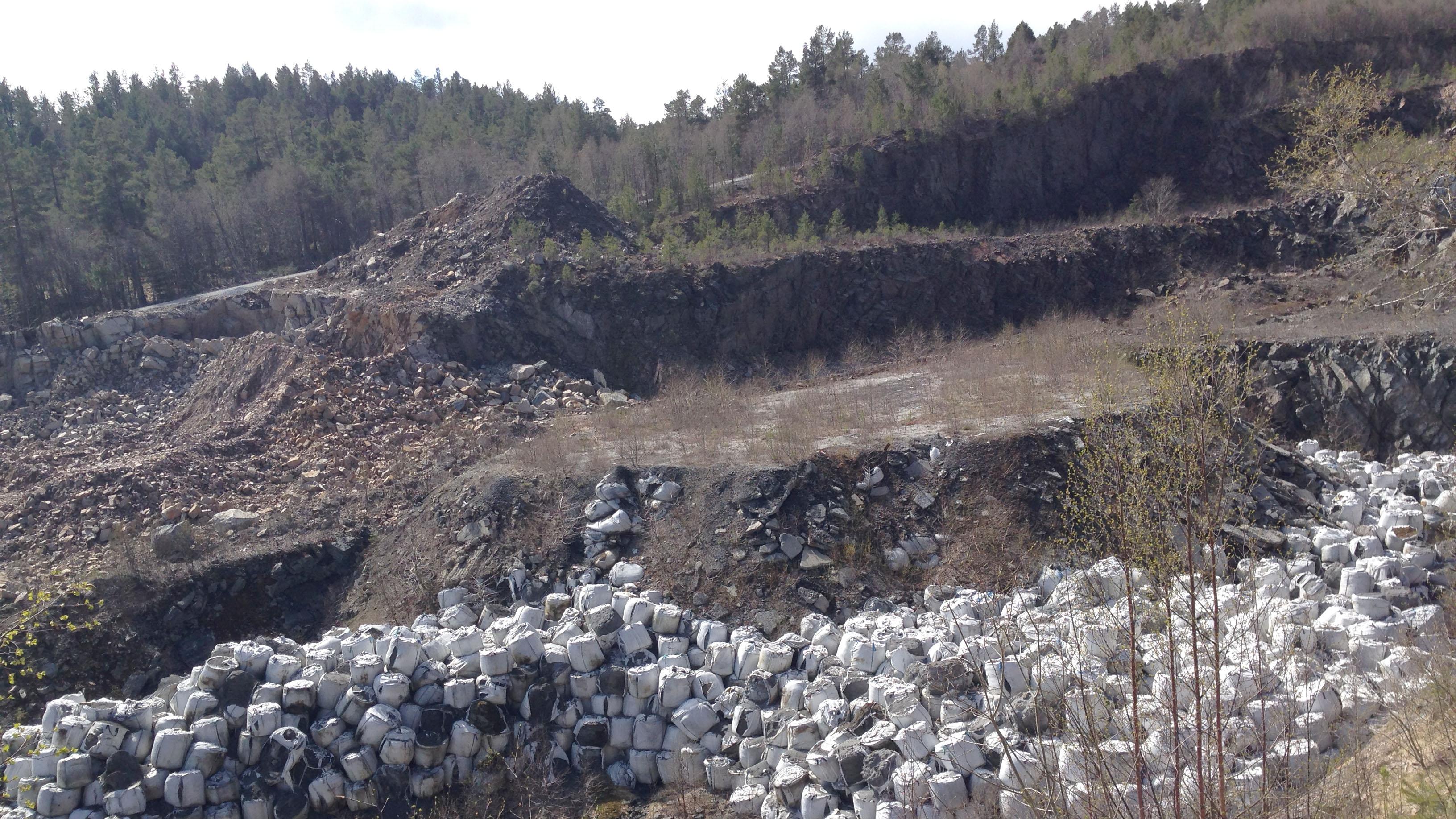 Bildet viser en grøft med mengde gamle sekker med møllestøv, avfall fra aluminiumsproduksjon.